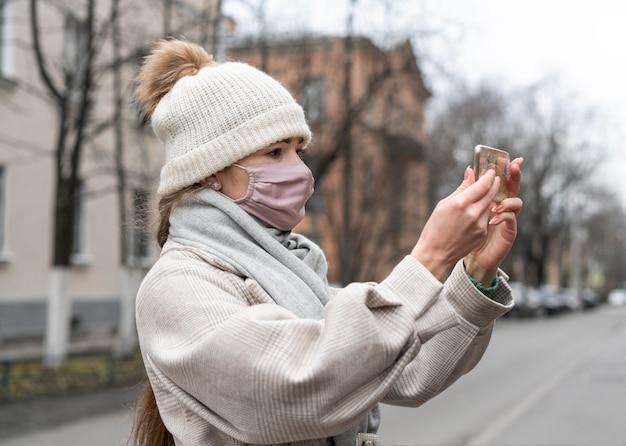 Vista laterale della donna con mascherina medica avente una videochiamata all'aperto