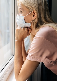 Side view of woman with medical mask at home looking through the window during the pandemic
