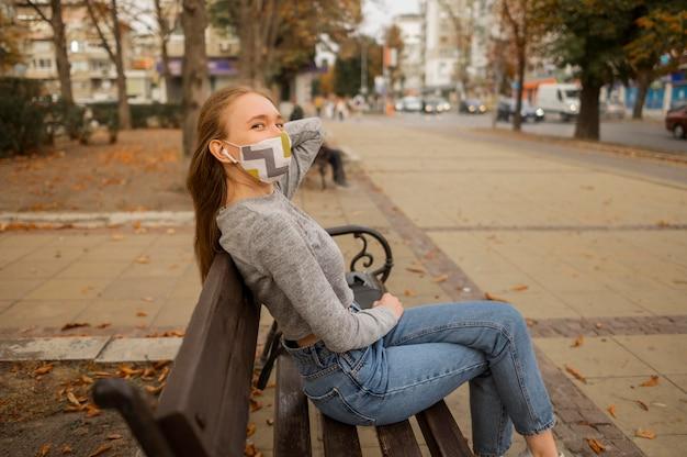 Donna di vista laterale con mascherina medica che si siede su una panchina