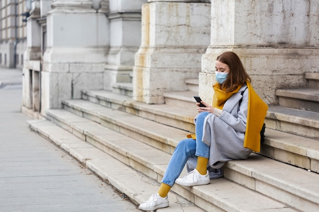 Side view of woman with medical mask sitting on steps outdoors and using smartphone