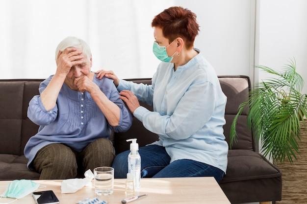 Side view of woman with medical mask taking care of an elder woman at home