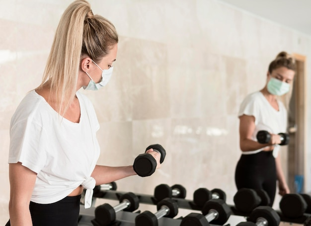 Side view of woman with medical mask using weights at the gym