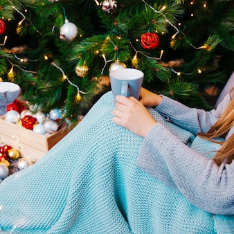 Side view of woman with mug of tea in front of christmas tree