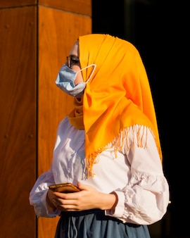 Женщина взгляда со стороны телефона маски