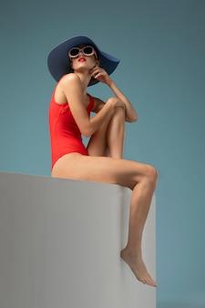 Вид сбоку женщина с красным купальником