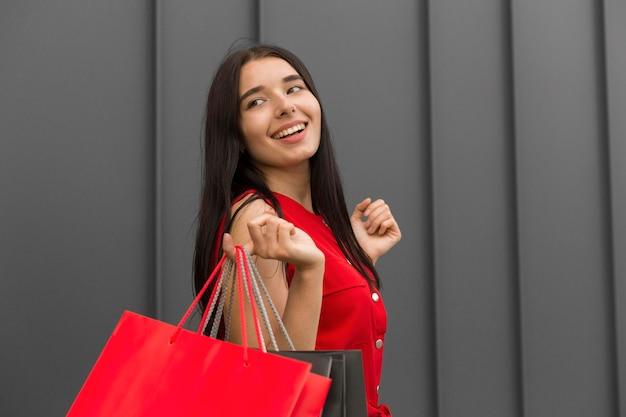 Donna di vista laterale con borse della spesa