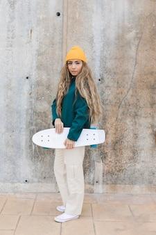 Vista laterale donna con skateboard