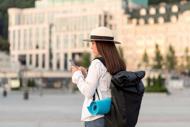 Vista laterale della donna con lo smartphone che viaggia con lo zaino