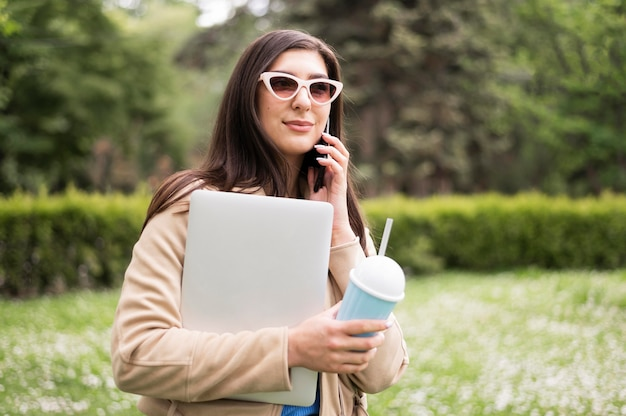 Side view of woman with sunglasses holding laptop and drink outdoors