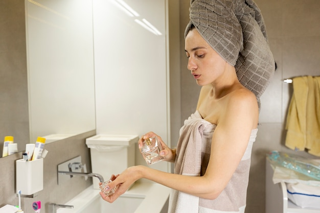 Side view woman with towel trying on perfume