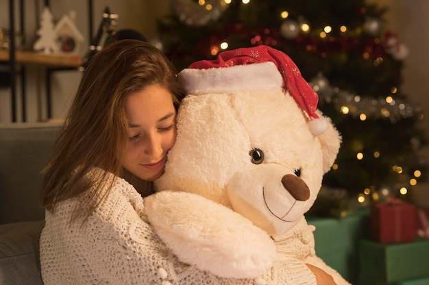 Side view of woman woman on christmas hugging her teddy bear