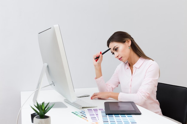 Side view of woman at work thinking and looking at computer