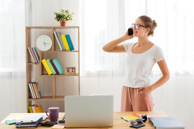 Side view of woman working from home and talking on phone
