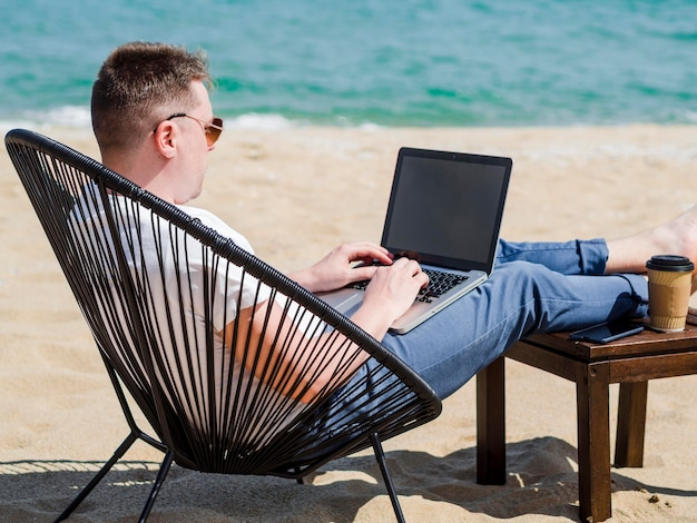Side view of woman working on laptop at the beach