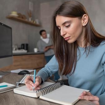 Vista laterale della donna che lavora nel campo dei media scrivendo roba sul taccuino