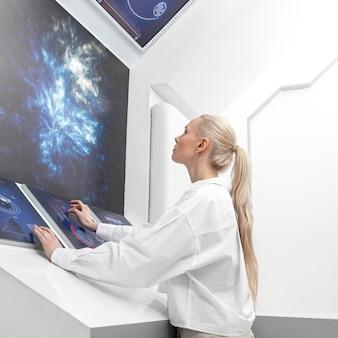デジタルモニターに取り組んでいる側面図の女性
