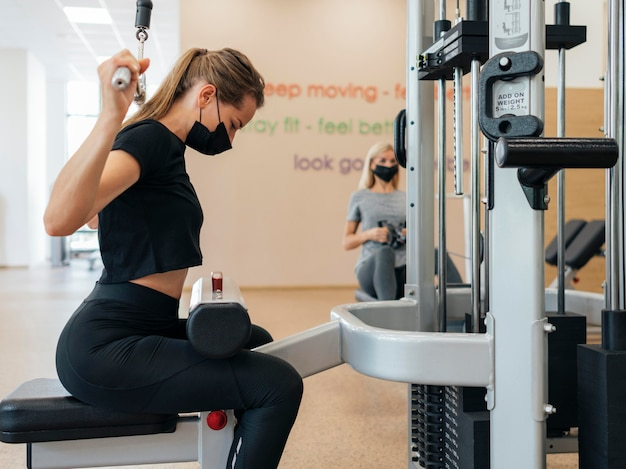 Side view of woman working out at the gym during the pandemic