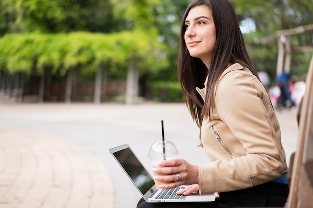 Side view of woman working outdoors on laptop