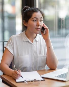 Donna di vista laterale che lavora al tavolo