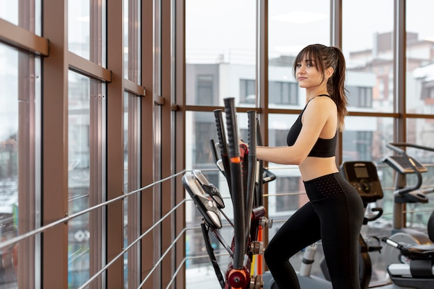 Side view woman working on treadmill