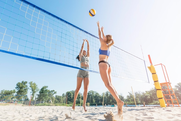Side view of women on the beach reaching for ball over net while playing volleyball