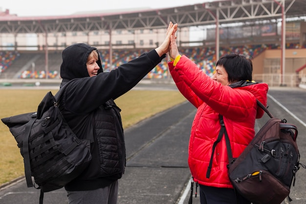 Side view women high five