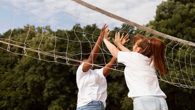 Side view of women high fiving each other over net