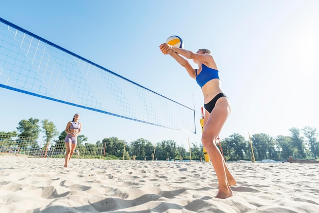 Side view of women playing beach volleyball