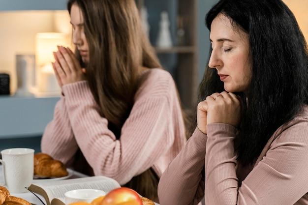 Vista laterale delle donne che pregano prima di cena
