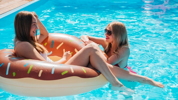 Side view women talking in pool