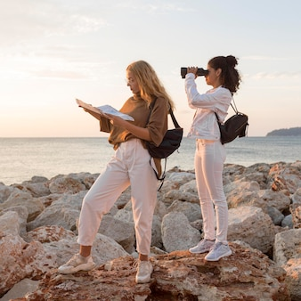 Side view women with map and binoculars