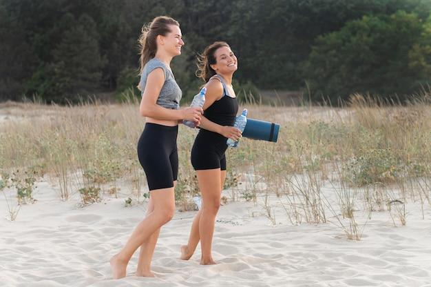 Vista laterale delle donne con bottiglie d'acqua che esercitano sulla spiaggia