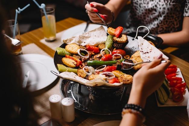 Le donne di vista laterale mangiano un tradizionale piatto azero di salvia di pollo con patate verdure e pane pita