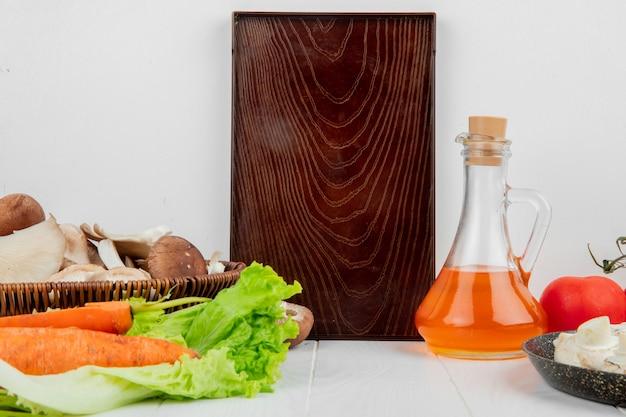 Vista laterale di un bordo di legno e dei funghi freschi in un canestro di vimini e nella bottiglia fresca delle carote di olio d'oliva su bianco