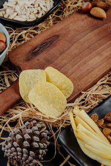 Side view of a wood board and potato chips on straw
