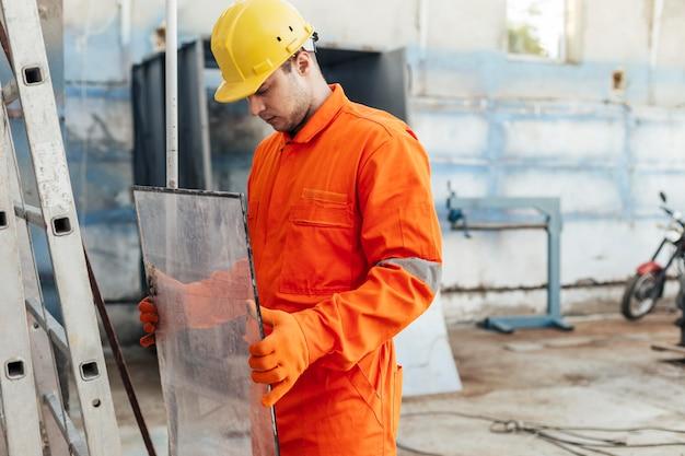 Vista laterale del lavoratore in uniforme con elmetto e guanti protettivi