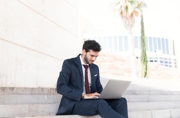 Вид сбоку рабочий человек сидит на лестнице