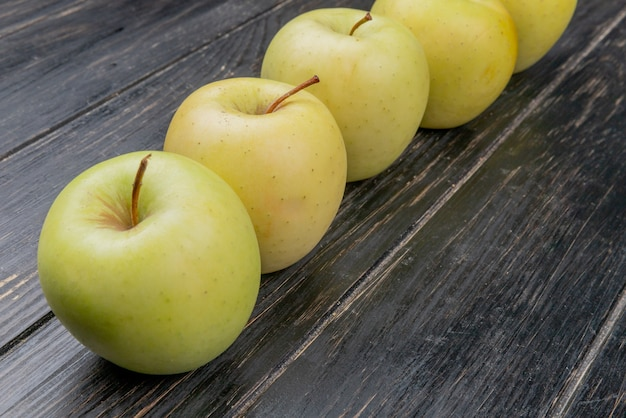 Side view of yellow apples on wooden background
