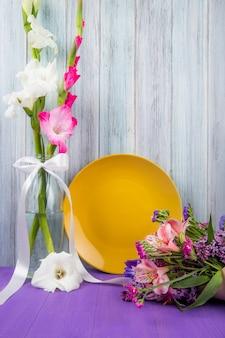 Vista laterale di un piatto di ceramica gialla con fiori di gladiolo di colore bianco e rosa in una bottiglia di vetro e con un bouquet di fiori che giace vicino su sfondo di legno grigio