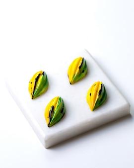 白いスタンドに黒い斑点のあるチョコレート菓子の側面図黄緑色
