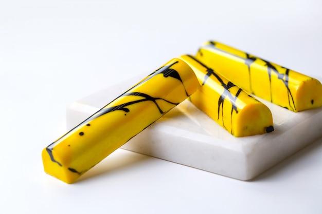 白いスタンドに黒い斑点のあるチョコレート菓子で黄色の側面図