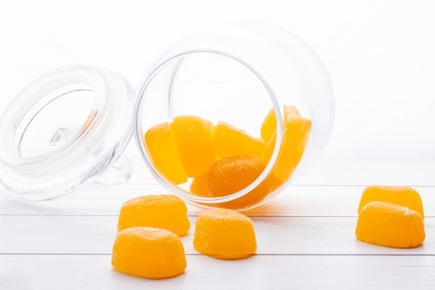 Side view of yellow marmalade candies scattered from a glass jar on white