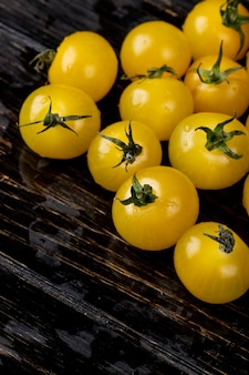 Side view of yellow tomatoes on wooden surface