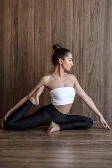Side view of a yogi woman doing a complex beautiful yoga pose in the gym