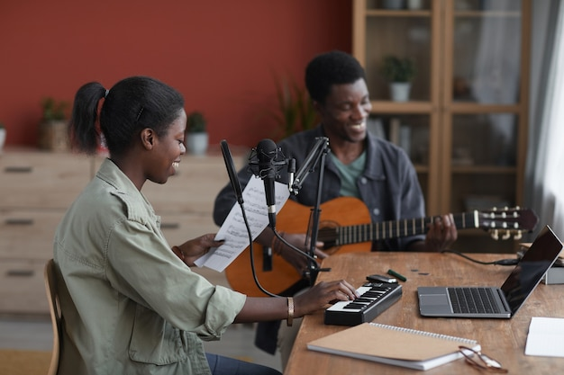 Side view at young african-american couple composing music together in home recording studio, copy space