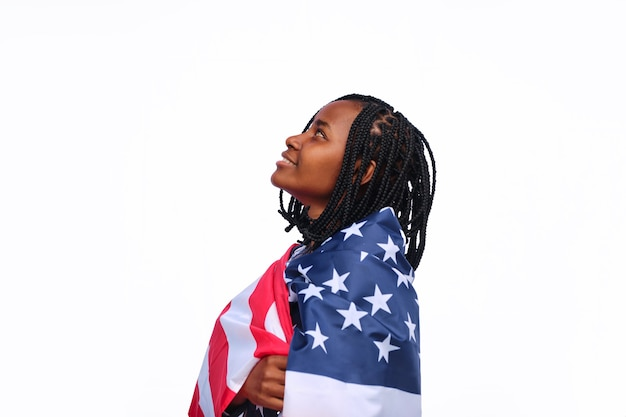 Side view of a young african american woman wrapped in usa flag looking up with against a white background.