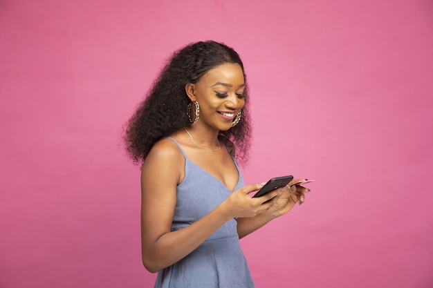 Side view of a young african female shopping online using her smartphone and credit card