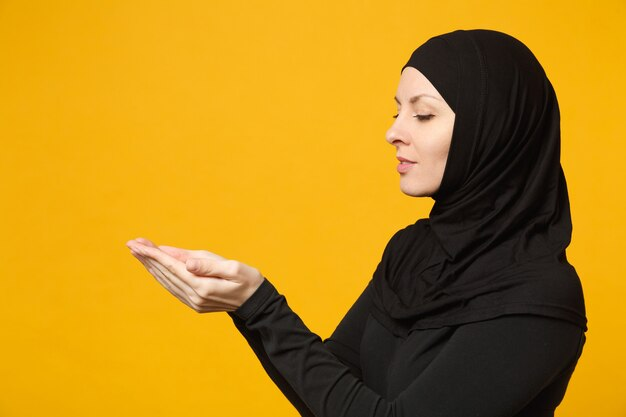側面図ヒジャーブの黒い服を着た若いアラビアのイスラム教徒の女性は、黄色の壁、肖像画で隔離の空のワークスペースを手に保持します。人々の宗教的なライフスタイルの概念。
