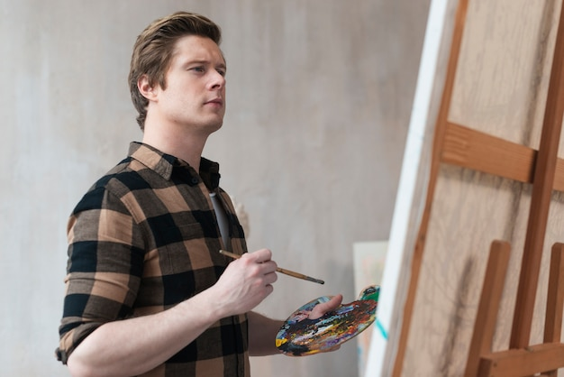 Vista laterale giovane artista dipinto su tela