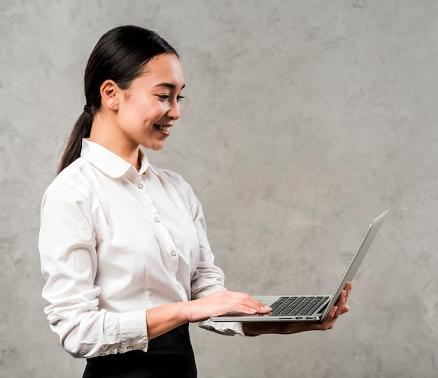 Side view of a young asian businesswoman looking at laptop holding in hand against grey background